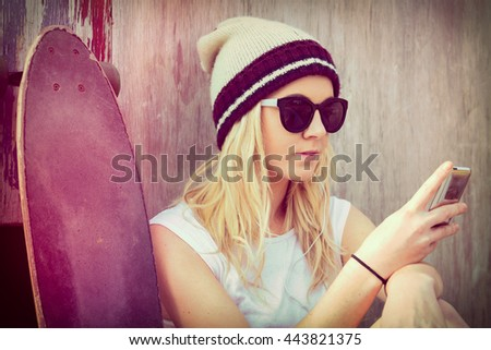 Skater girl with mobile device - stock photo