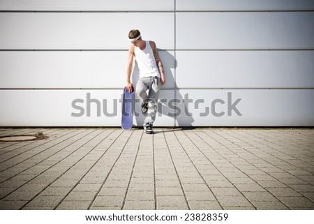 skater holding his skateboard while taking a break - stock photo