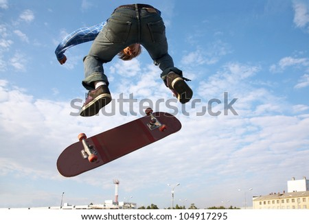 Skater jumps high in air on background blue sky - stock photo