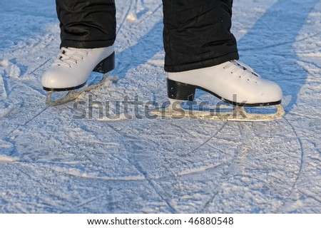 skater's legs standing on winter ice rink - stock photo