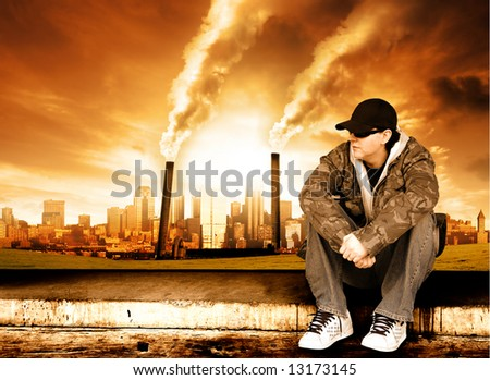 Skater sits in front of a polluted city - stock photo