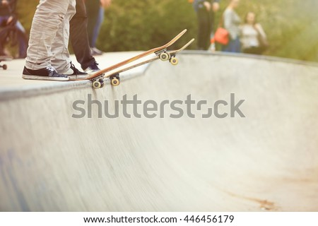 Skater standing on a ramp in skate park ready to ride skate board and do tricks. Concrete outdoor park, focus on skateboard, feet and shoes