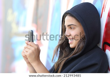 Skater style teen girl reading happy her smart phone with an unfocused graffiti wall in the background - stock photo