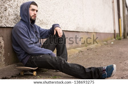 Skater with hood up sitting on his board looking thoughtful outside the skate park - stock photo