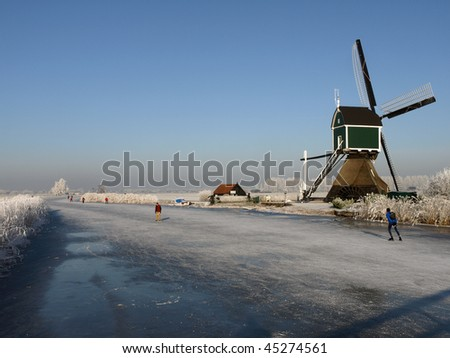 Skaters on the ice at Kinderdijk, The Netherlands. Several windmills visible against a clear blue sky. - stock photo