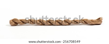 Skein of twisted cotton thread or string made with natural fibers lying stretched out straight on a white background with copy space