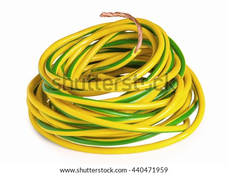 Skein of  yellow green copper wire in insulation isolated on white. Technology and industry concept. - stock photo