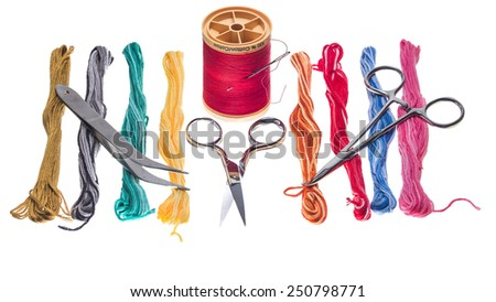 Skeins of brightly colored embroidery floss accompanied by sewing tools - stock photo