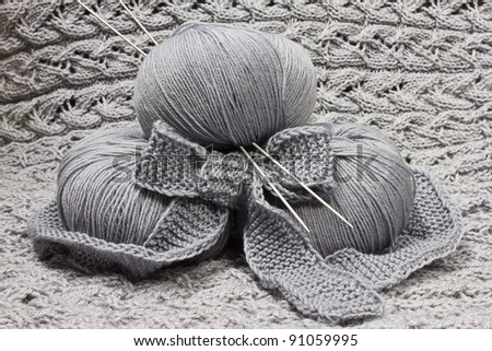Skeins of knitting with knitting needles on pattern background