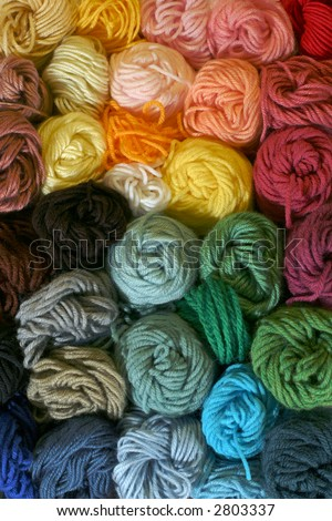 Skeins of Yarn - Vertical - Practical and colorful storage of skeins of yarn being used for different knitting, crocheting, and needle-point canvas projects. - stock photo