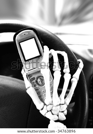 skeletal hand texting while driving - stock photo