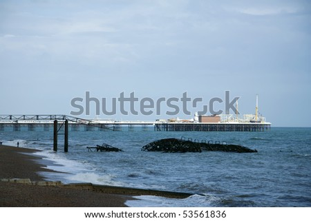 skeletal remains of west pier with palace pier in background, brighton beach, england - stock photo