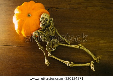 Skeleton and pumpkin Halloween concept on wooden background. Dark tone - stock photo