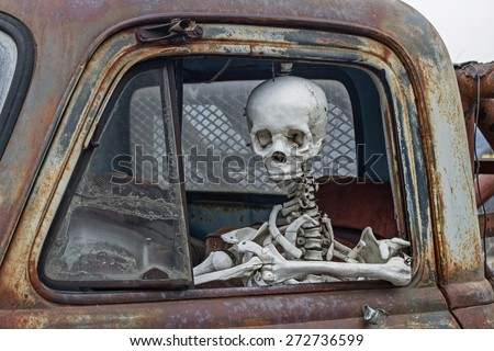 skeleton at the wheel of an old junk cars - stock photo