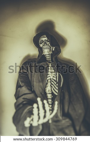 Skeleton Beggar. Skeleton in hoodie with hand reaching out as if begging. Shot with spot lighting and edited with vintage filters. - stock photo