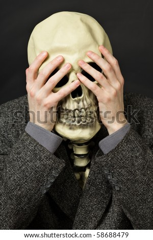 Skeleton covering his eyes on a dark background - stock photo