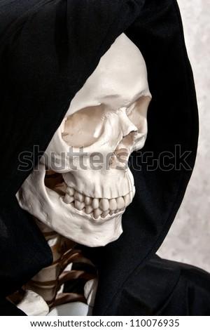 Skeleton face in a black grim reaper hood - stock photo