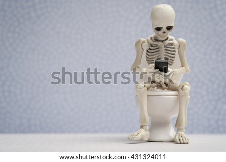 Skeleton getting busy with his smartphone while sitting on water closet