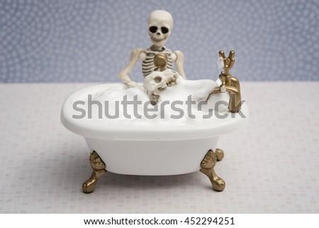 Skeleton giving bubble bath to his dog - stock photo