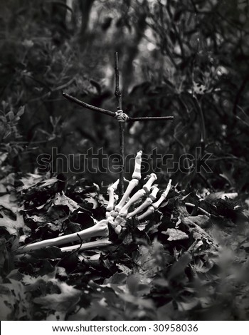 skeleton hand coming out of the ground, reaching for a crudely made cross - stock photo