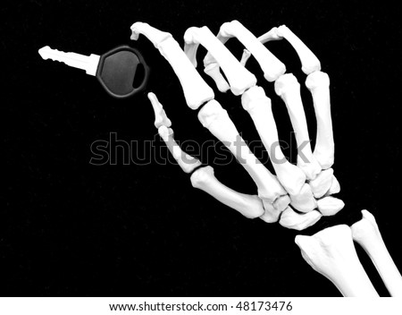 skeleton hand with car key - concept of reckless driving or road rage - stock photo
