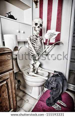 Skeleton handling the paperwork in the bathroom.  The crow has died from the fumes. HDR. - stock photo