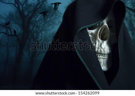 Skeleton in a black hood. Mystical image. - stock photo