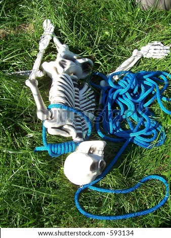Skeleton in a noose on the grass - stock photo