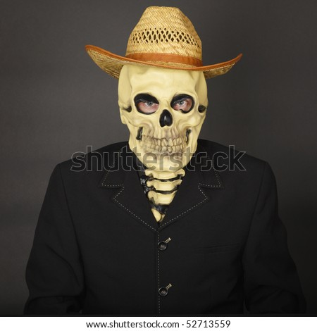 Skeleton in a straw hat on a dark background - stock photo