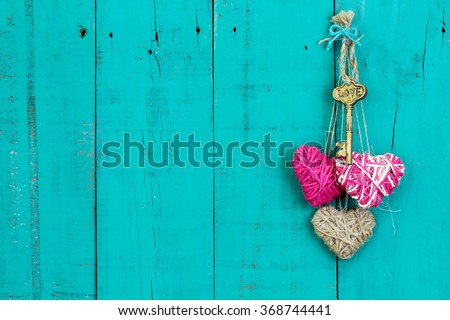 Skeleton key, pink and natural rope hearts hanging on antique rustic teal blue wood door; Valentine's Day and love concept - stock photo