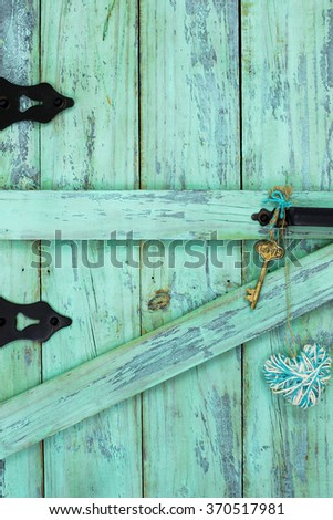 Skeleton key with Love and teal blue rope heart hanging  on antique mint green rustic wood door - stock photo