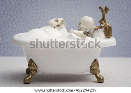 Skeleton kid and skeleton dog getting bath - stock photo