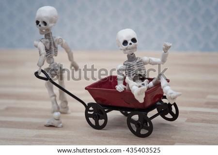 Skeleton kids playing toy wagon - stock photo