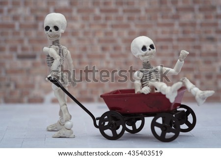 Skeleton kids playing toy wagon with brick wall background - stock photo