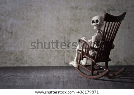 Skeleton looking back while sitting in the rocking chair - stock photo