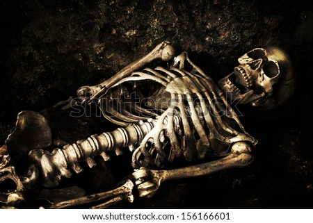 Skeleton lying in shallow grave at Halloween - stock photo