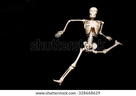 Skeleton model action on black background. - stock photo