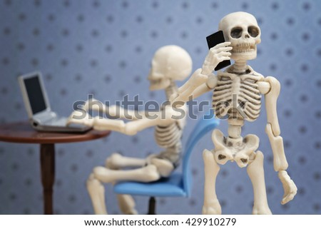 Skeleton talking on the phone while his friend working on a laptop