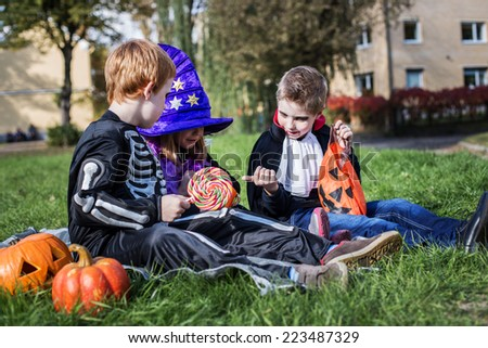 Skeleton, witch and vampire sharing Halloween candies. Outdoor portrait  - stock photo