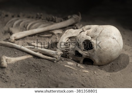 skeleton with skull of human being on sand - stock photo