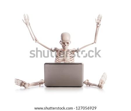 Skeleton working on laptop - stock photo