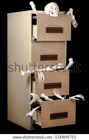 Skeletons in a cabinet are partially revealed in this low key image. - stock photo