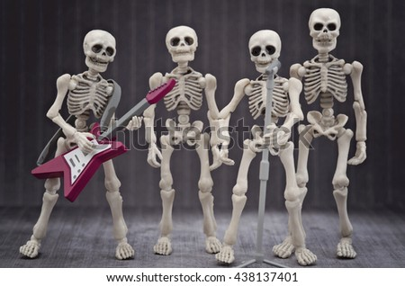 Skeletons in pose as a rock band - stock photo