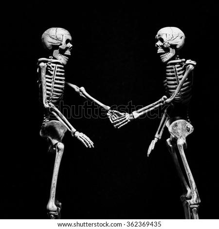 skeletons shaking hands - stock photo
