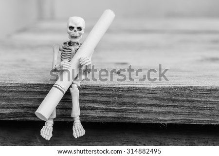 Skeletons with cigarette sit on wood table , selective focus - stock photo