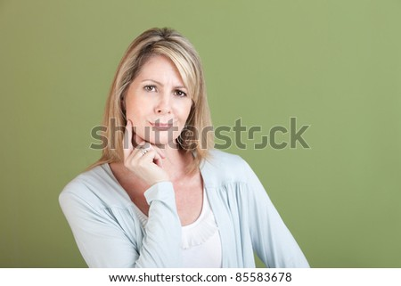 Skeptical mature woman with finger on chin over green background - stock photo