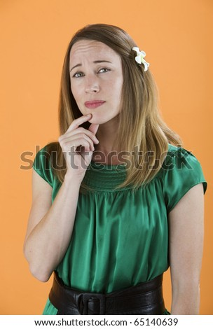Skeptical or nervous woman with hand on her chin - stock photo