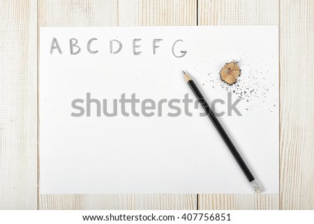 Sketch artist  work place with soft black pencil and shavings. First hand-drawn letters of the alphabet on white paper. - stock photo