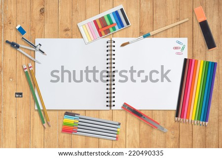 Sketch book and paint tools on wood background - stock photo