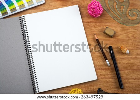Sketchbook pencil and eraser on the table - stock photo